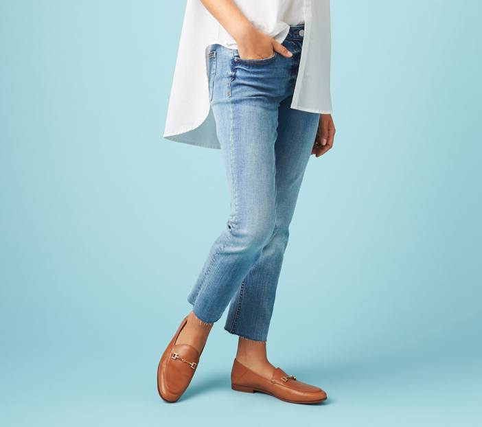 White high-low shirt with raw hem ankle length jeans and brown loafer shoes.