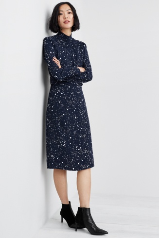 Outfit including a black and white speckled midi dress with black booties.