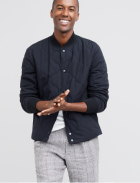 Men's clothes including a white tee under a black quilted jacket with grey plaid pants.