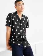 Men's clothes including a black and white polka dot collared shirt with dark wash jeans.