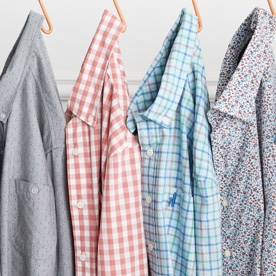Shirts in a variety of prints hung on a rack.