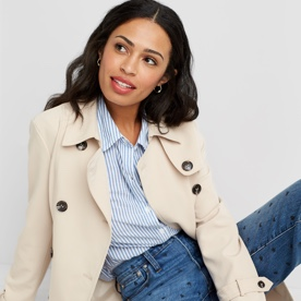 Size inclusive clothing including a light blue shirt, ivory trench and jeans.