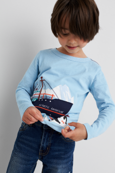 Kids clothes including a blue shirt with boat graphic and jeans.
