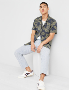 Men's clothes including blue and green palm print shirt over a white tee with grey ankle pants and white sneakers.
