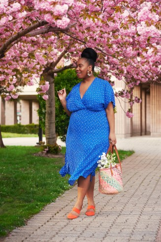 Women's outfit including orange flats, tote bag and plus size Katie Sturino blue print dress with V-neck and flutter sleeves.