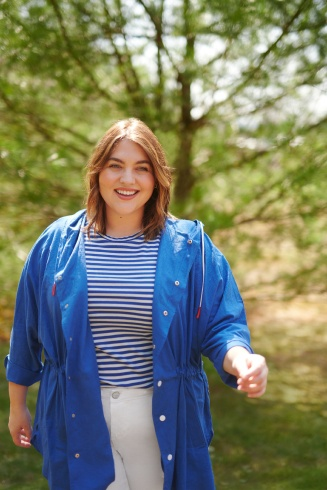Women's plus-size outfit including white skinny jeans and Katie Sturino blue windbreaker jacket over a blue and white striped tee.