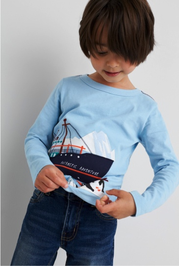 Jeans and a long sleeve light blue graphic tee with boat design.