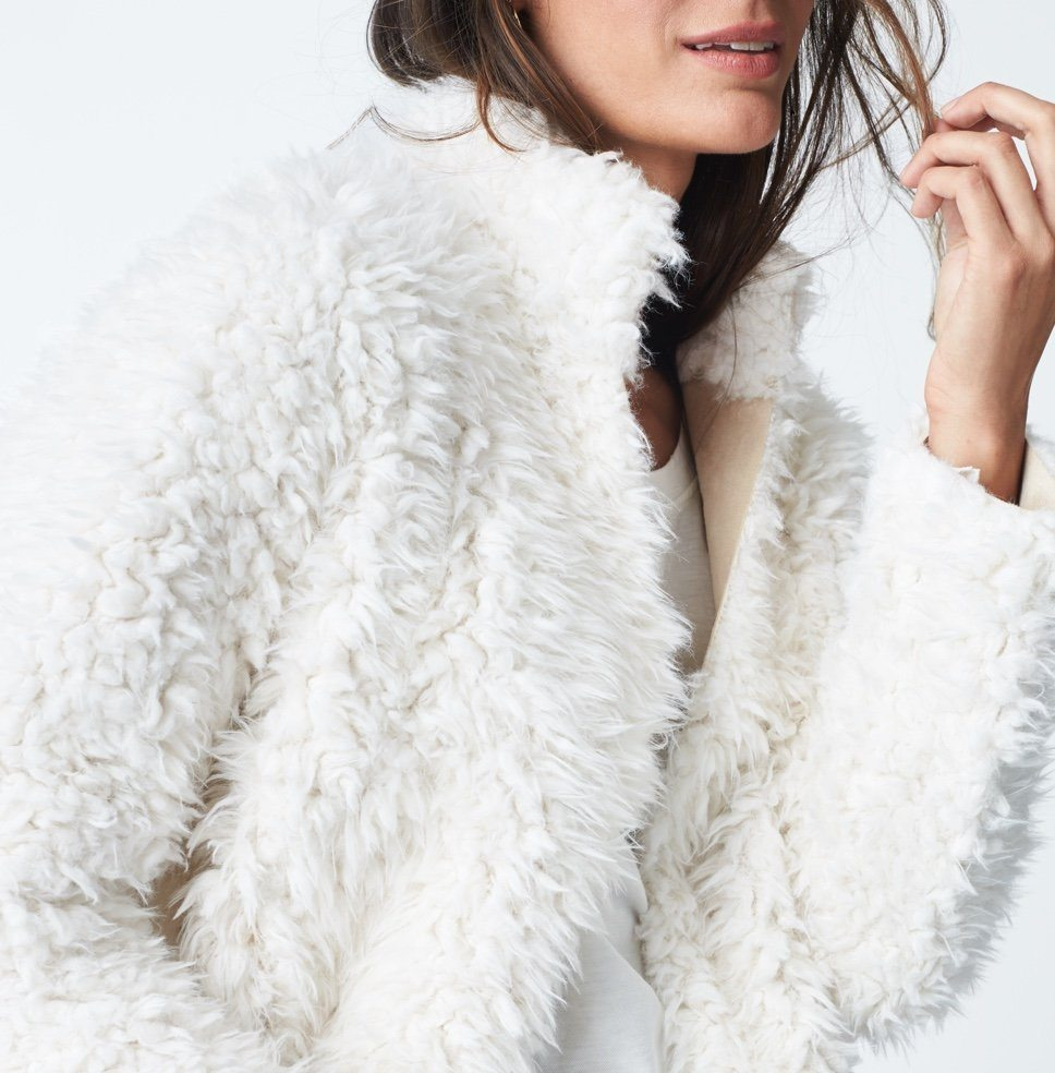 White faux fur jacket and white tee.