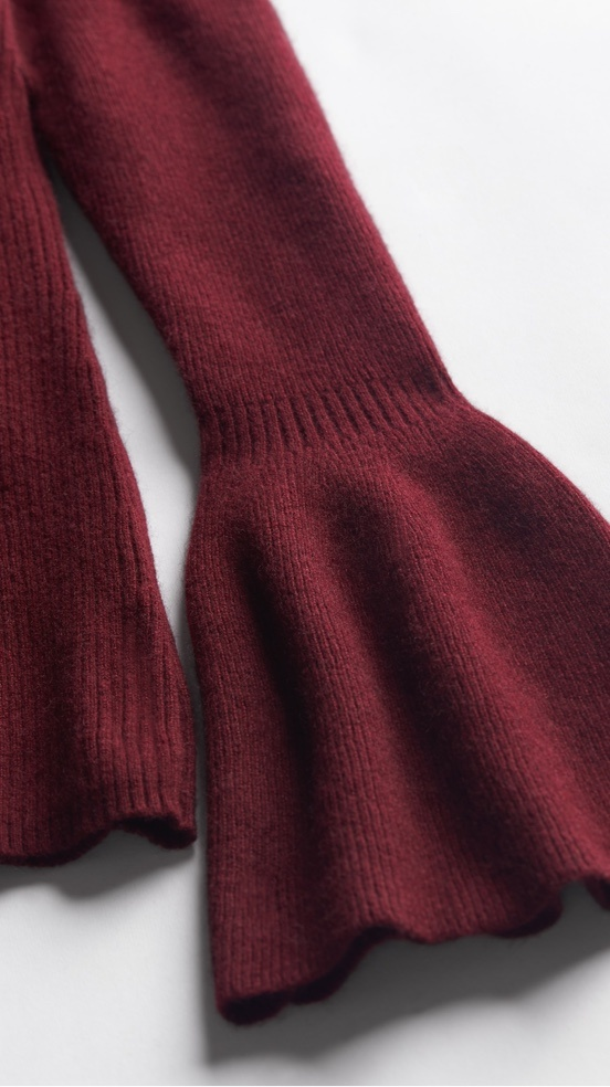 Bell sleeve of a maroon sweater.