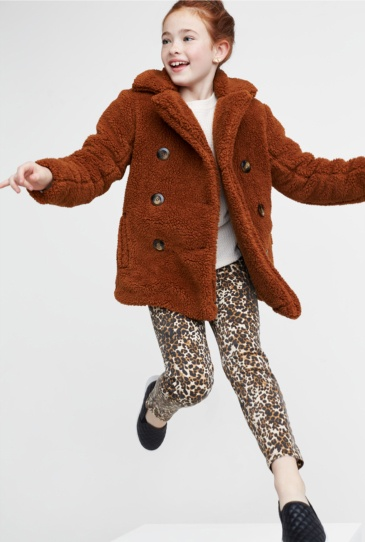 Brown fleece coat with white tee, leopard print pants and black shoes.