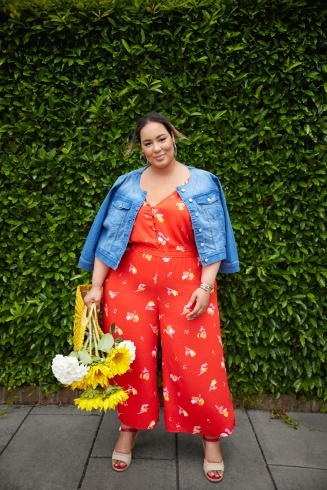 Women's outfit including a medium wash denim jacket, white heels and plus-size Katie Sturino red floral V-neck jumpsuit.