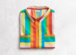 Rainbow striped button down top, folded.