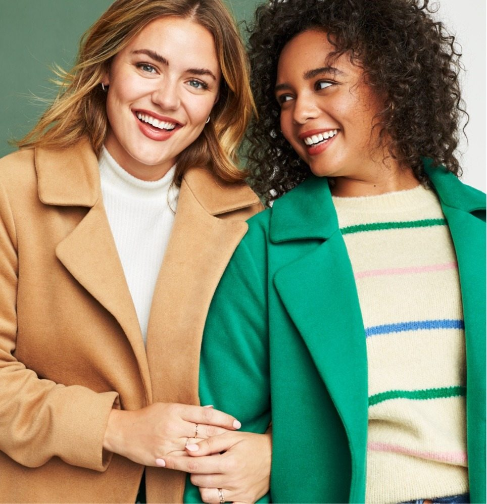 Plus size and size inclusive clothing including a white sweater with tan coat, and striped sweater with green coat.