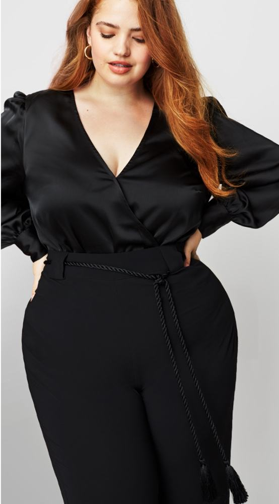 Size inclusive outfit including black plus size pants with tie detail and black v-neck blouse with puff sleeves.