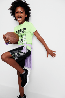 "Kids clothes including a green ""game time"" graphic tee, black and camo print shorts and black sneakers."