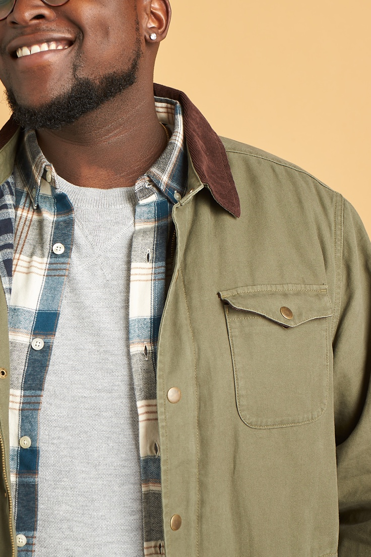 Grey tee, plaid shirt and olive green jacket with brown collar.
