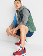 Men's clothes including a grey hoodie sweatshirt, green vest, blue shorts and red sneakers.
