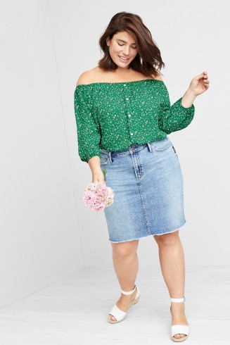 Outfit including a green floral off the shoulder top with denim skirt and white sandals.