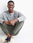Men's clothes including a grey sweatshirt over a grey and orange tee with green joggers and white sneakers.