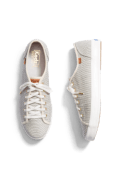 Women's light grey lace-up sneakers with brown leather detail.