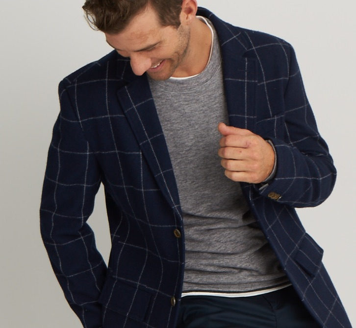 Male model wearing navy blazer with grey stripes and grey t-shirt.