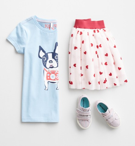 Stitch Fix Kids outfit including a light blue dog graphic tee, white and pink print skirt and white velcro sneakers.