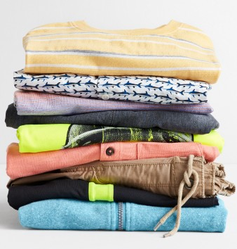 A stack of Stitch Fix Kids clothing including shirts, shorts, zip jackets and graphic tees.