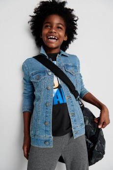 Stitch Fix Kids clothes including a black graphic tee, jean jacket, grey pants and black crossbody bag.