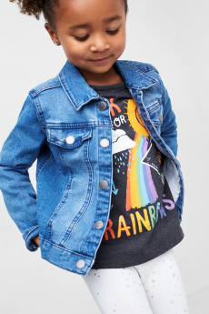 Kids clothes including a denim jacket, rainbow tee and white pants.