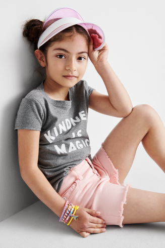 Stitch Fix Kids outfit including a pink visor, grey graphic tee with pink cutoff shorts.