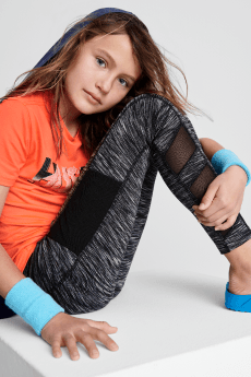 Kids athletic wear clothes including an orange graphic tee, black and grey workout pants with mesh detail and blue shoes and wrist guards.