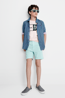 Kids clothes including a pink graphic tee, blue plaid short and green shorts with grey sneakers and sunglasses.