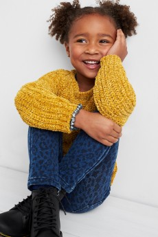 Stitch Fix Kids clothes including a yellow sweater and blue leggings with black shoes.