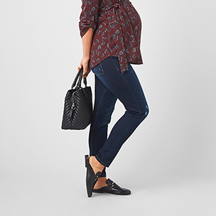Maroon printed shirt with dark wash jeans, black handbag and mule shoes.