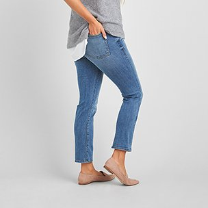 Grey and white top with medium wash ankle length jeans and nude flat shoes.