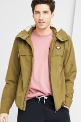 Stitch Fix men's outfit including a pink tee, tan windbreaker jacket and black jogger sweatpants.