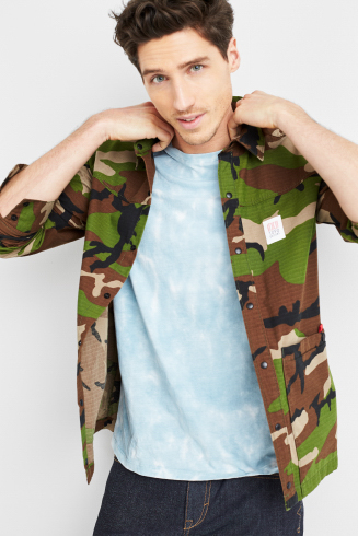 Stitch Fix men's outfit including a light blue tee under a camo print button shirt jacket with dark wash jeans