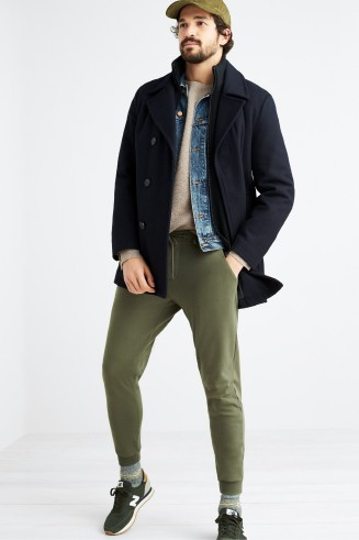 Stitch Fix men's clothes including cream t-shirt, denim shirt, blue coat, green joggers and green sneakers.