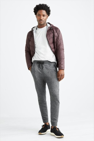 Stitch Fix men's athleisure clothing including a white t-shirt, burgundy puffer jacket, grey jogger pants and black sneakers.