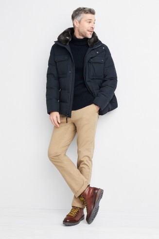 Stitch Fix men's clothes including a black sweater, navy puffer jacket, tan pants and brown boots.
