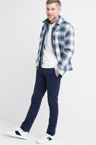 Stitch Fix men's clothing outfit including a blue and white plaid button shirt over a denim button shirt and white tee with dark wash denim pants and white sneakers with black detail.