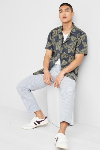 Stitch Fix men's clothing outfit including a green and navy tropical print button collared shirt over a white tee with cropped grey pants and white sneakers with blue detail.