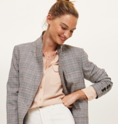 Grey check blazer over a peach shirt with white bottoms.