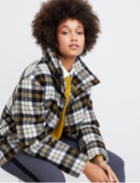 Yellow top with yellow and black plaid jacket with grey pants.