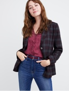 Plum top under plaid blazer with medium wash jeans.
