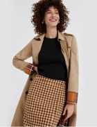 Brown plaid skirt, tan trench coat and black top.