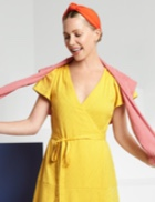Yellow v-neck dress with pink and orange accessories.