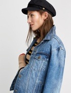Tan and black top with denim jacket and black hat.