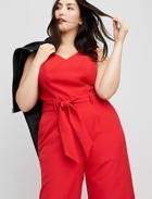 Red jumpsuit with tie detail and black jacket.
