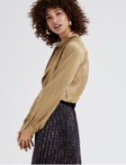 Gold blouse with dark floral skirt with pleating.